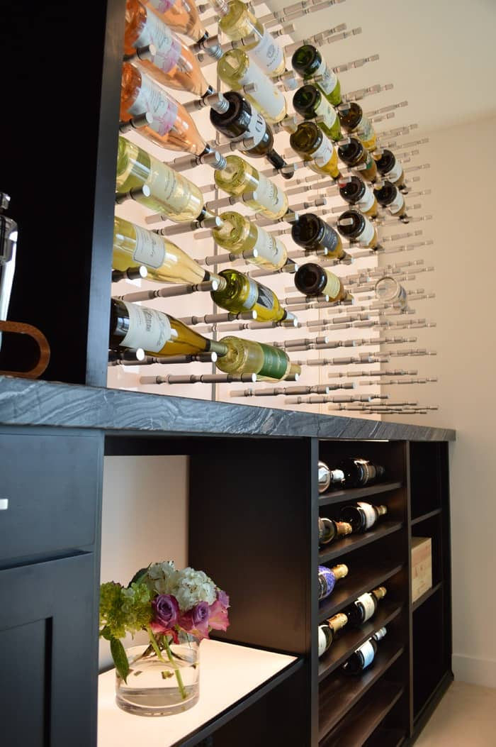 A fusion of modern design and traditional design... This wine room has a classy wooden wine shelf and contemporary brushed metal wine pegs.