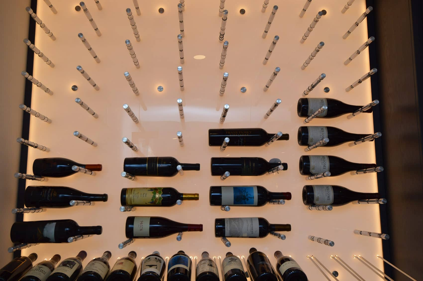 Adding a Reveal rack at the bottom of the wine pegs maximizes the space usage for the modern wine room.