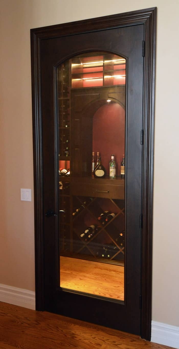 Dark finish for this wooden wine cellar door complements the brownish red ambiance of the wine cellar interior.