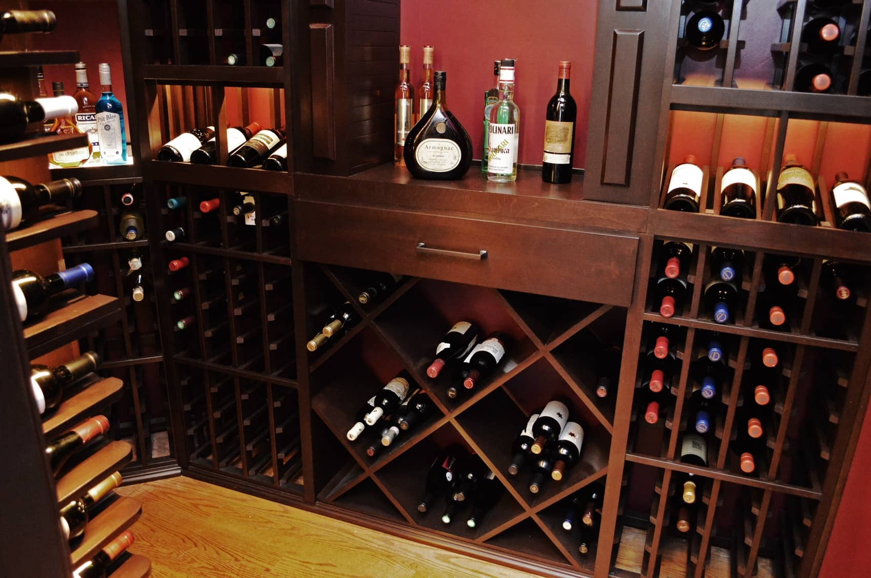 Diverse wooden wine racking designs used for this project gives the owner flexibity what wines and liquors he can store with it.