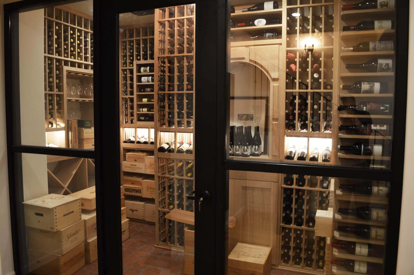 Framed glass doors gives a touch of modern design for this traditional wine cellar.