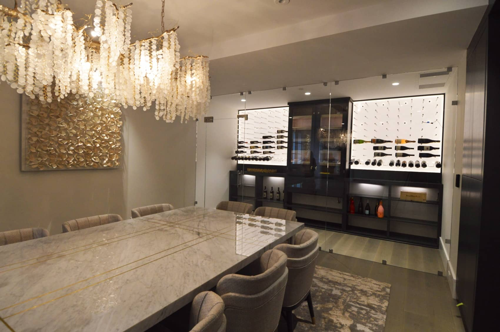 Intricate ornaments and accessories in the dining room serves as an accent to the minimalist design of the glass wine room.