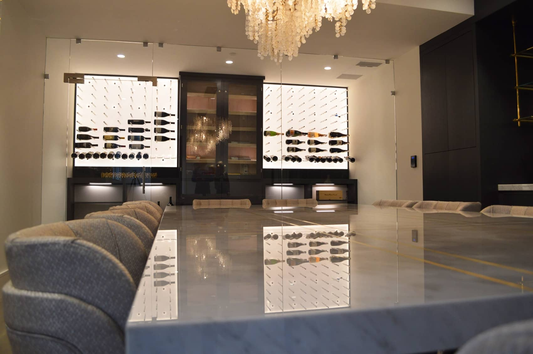 Light coming from the wine cellar reflects to the polished surface of the marble table. The spontaneous reflection of light in the wine room and the dining room adds more contemporary element in it.