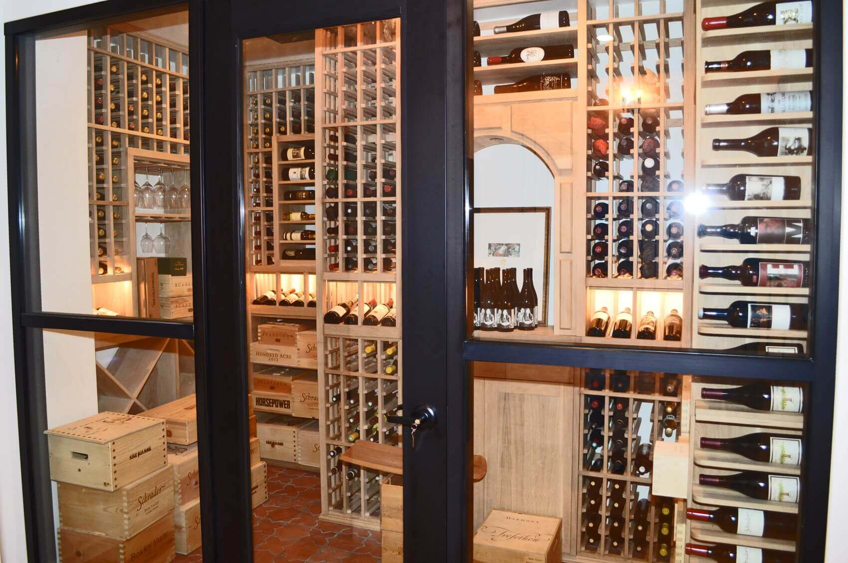 The framed glass doors at the wine cellar entrance gives a welcoming thought to the visitors of the wine room.