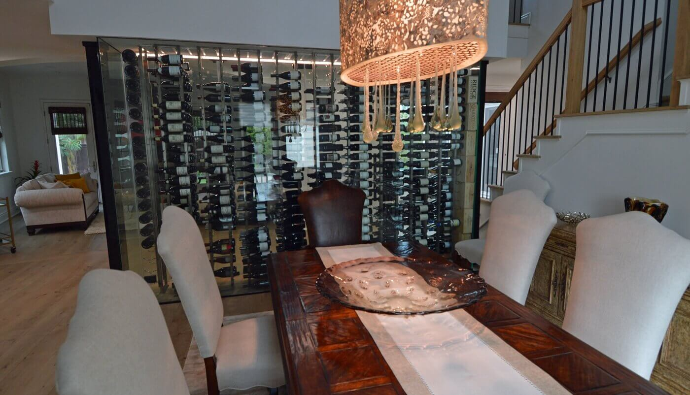 The traditional feel from the dining table and the chandelier complements well with the contemporary glass wine wall.